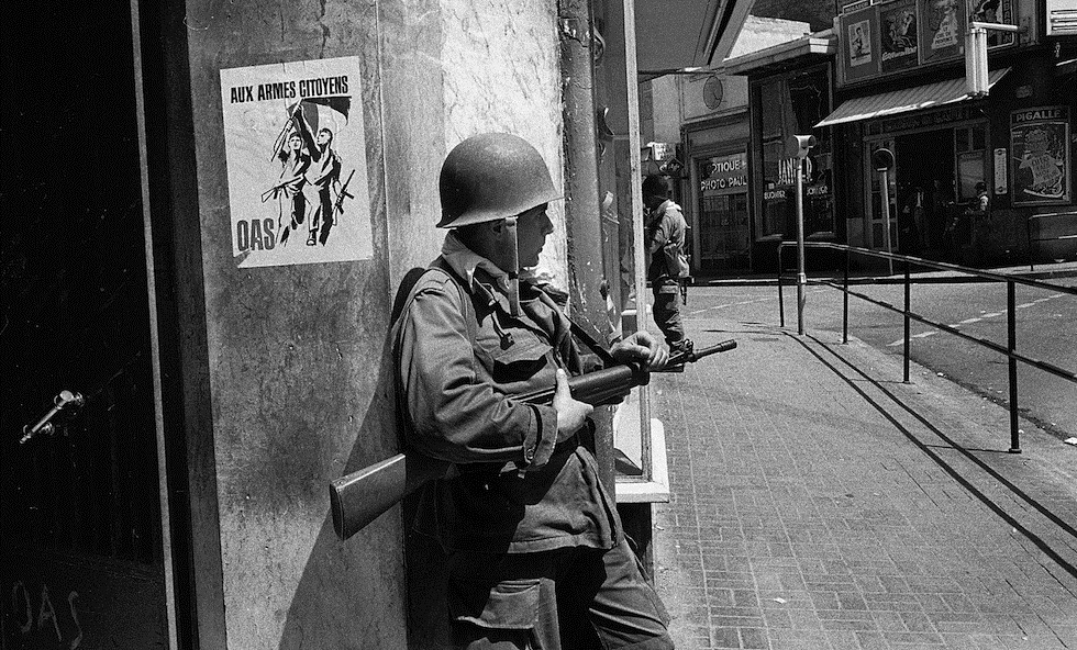 A French soldier guards a street corner in Oran, Algeria, May 15, 1962. On the wall is a poster of the right-wing nationalist Secret Armed Organization, calling for citizens to take up arms against Algerian independence. (AP Photo/Horst Faas)