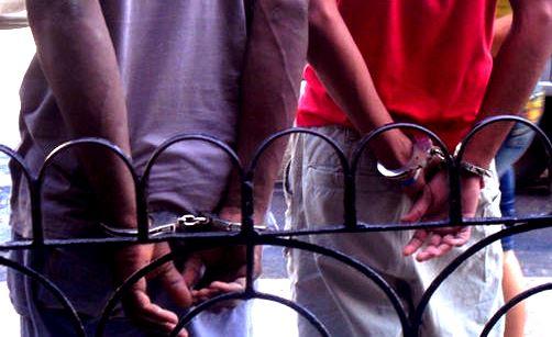 Hombres esposados ammanettati Foto-Luz Escobar
