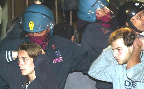 FILE - Italian riot police arrest unidentified anti-G8 protestors following the violent police raid in the A. Diaz school where they were housed during the Group of Eight meeting, Genoa, northern Italy, July 22, 2001. Over 60 people were injured during the raid and over 90 arrested for alleged involvement in the violence which struck Genoa July 20-22. Detained protestors have filed reports accusing Italian police forces of physical and psychological violence. (AP Photo/Luca Bruno)